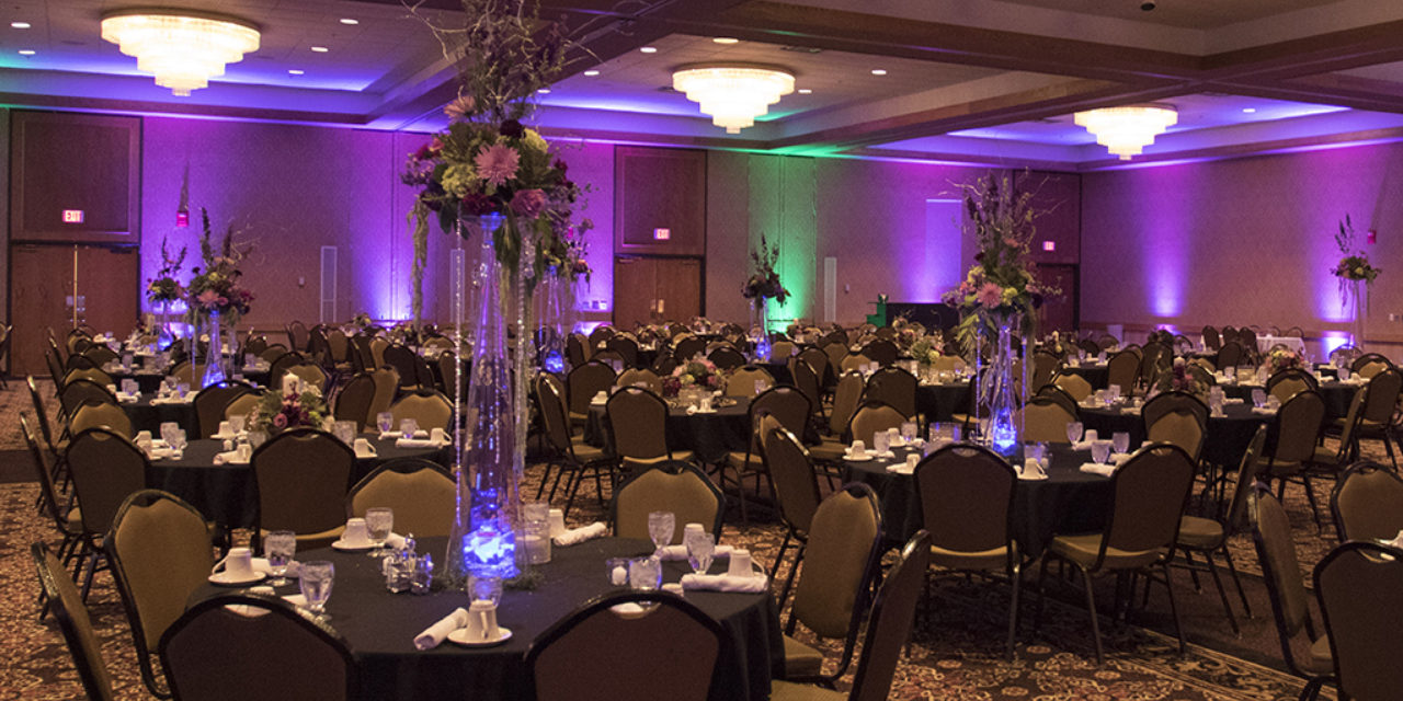 Event room decorated for wedding. Purple and green lighting.