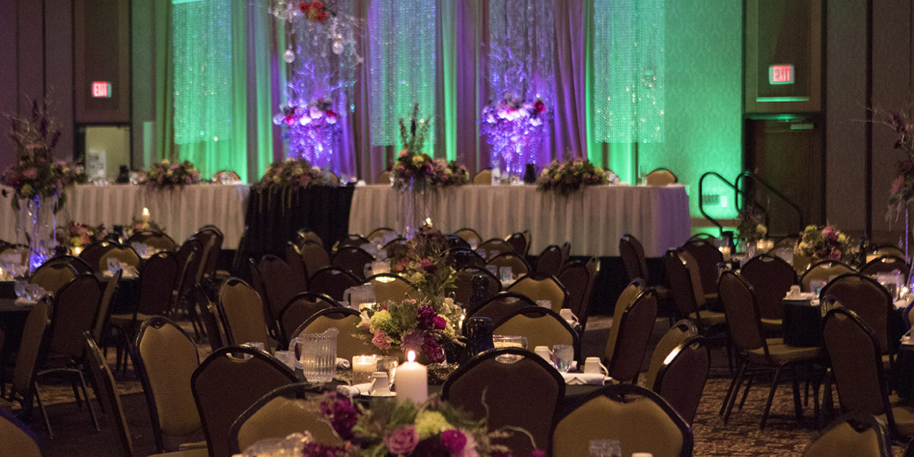 Event room decorated for a wedding. Purple and green lighting and tables decorated.