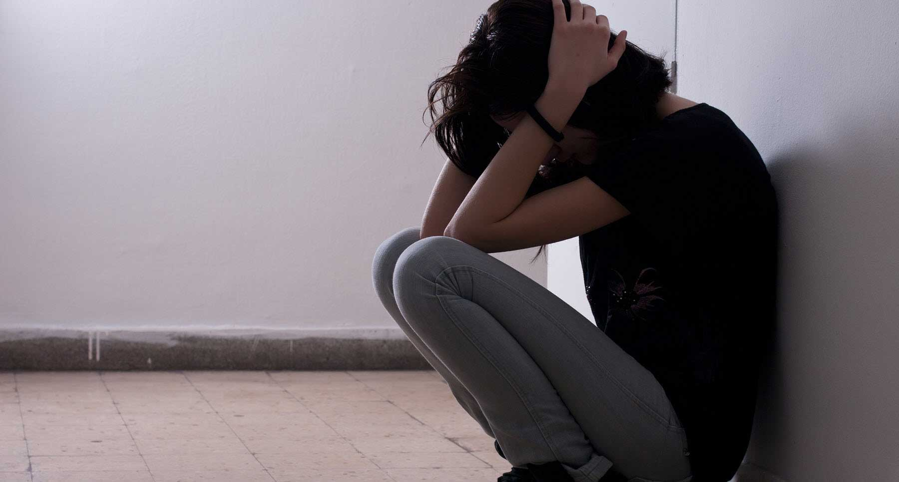 Girl holding her head because she hates herself. What to do when you hate yourself from TheHopeLine