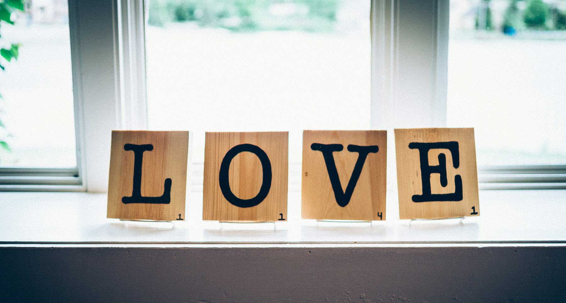 scrabble tiles that spell love on a window sill