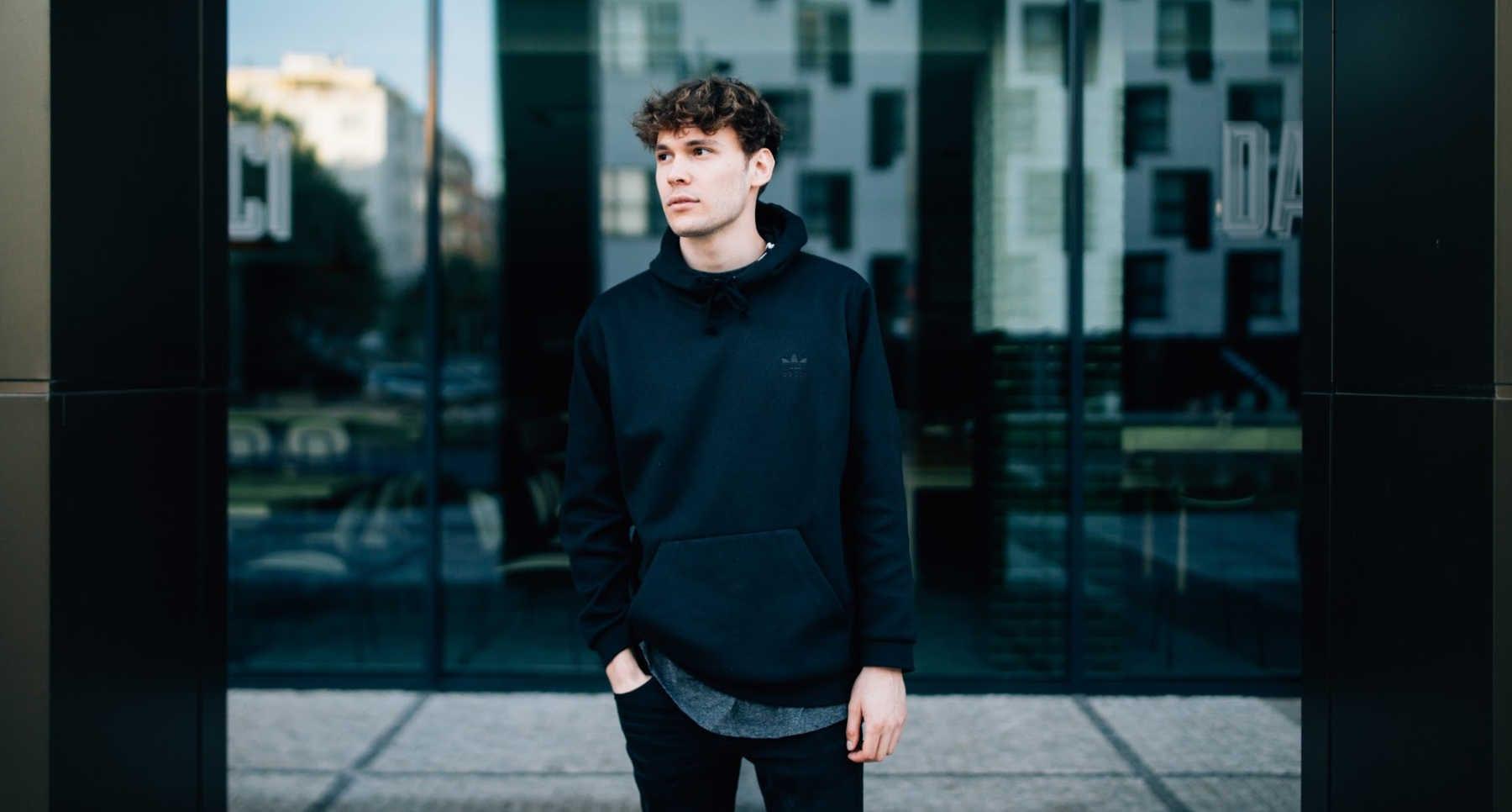 boy in black hoodie in front of building
