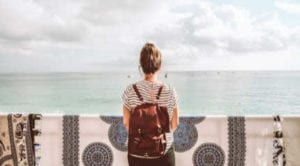 girl with backpack facing ocean