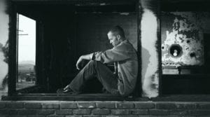 Guy sitting against a wall looking down struggling with depression
