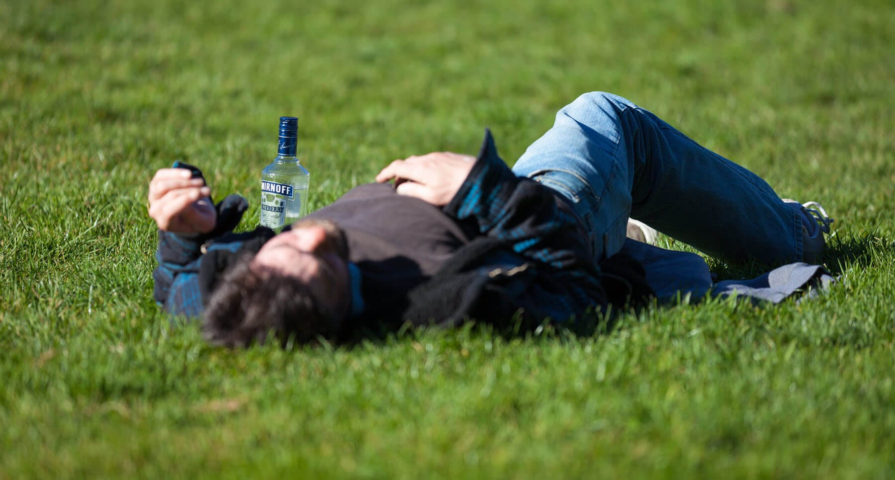 Guy laying on ground struggling with a relapse in his addiction