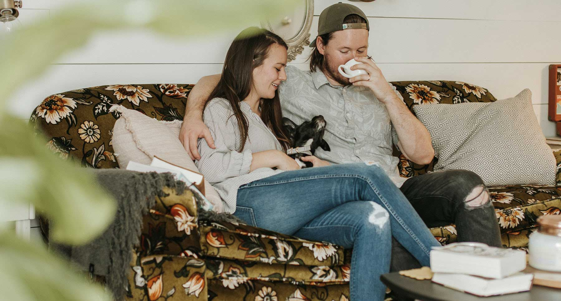 couple-sitting-on-sofa-with-their-dog-enjoying-a-healthy-relationship