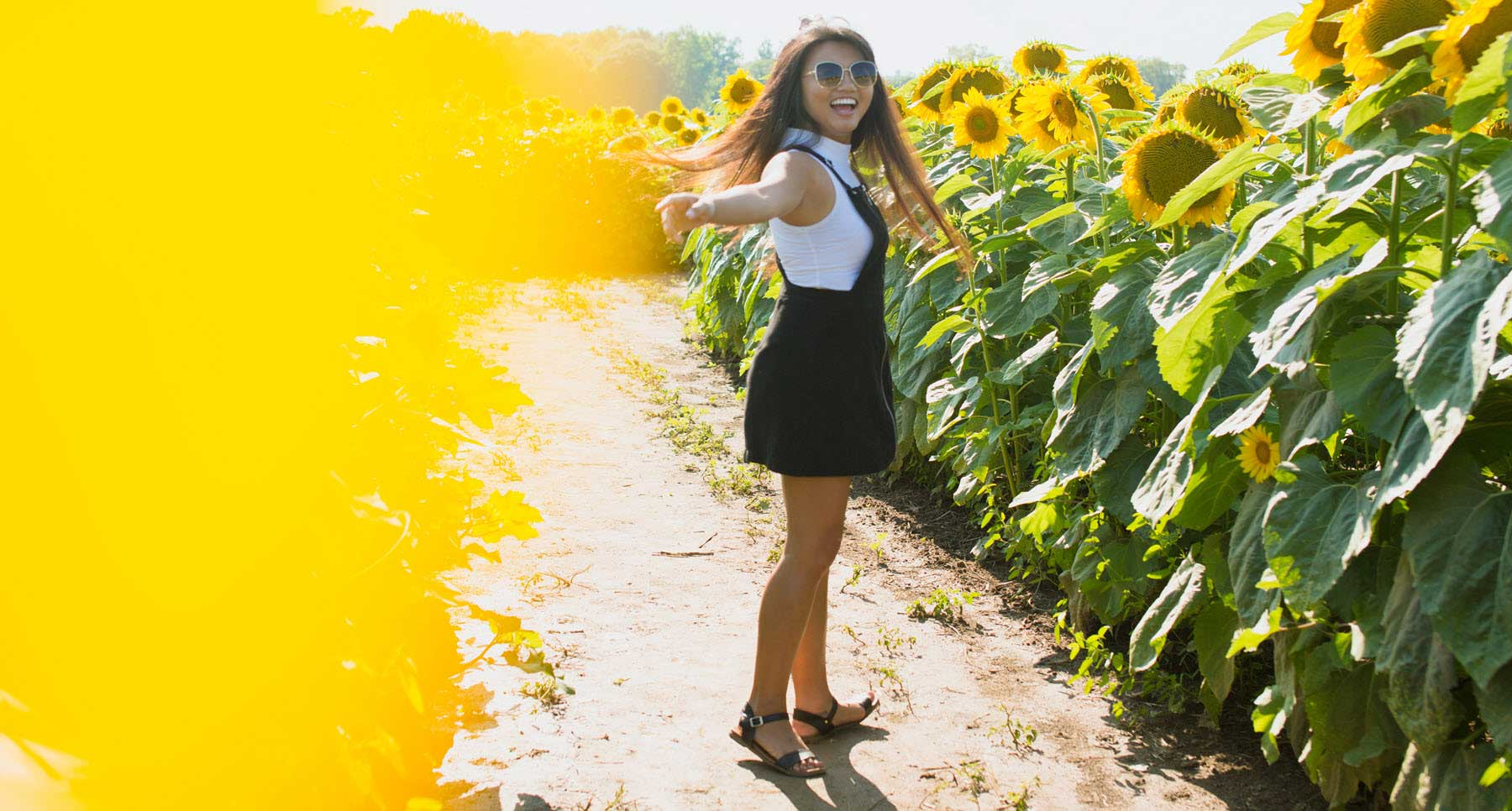 Girl-smiling-in-a-field-of-sunflowers