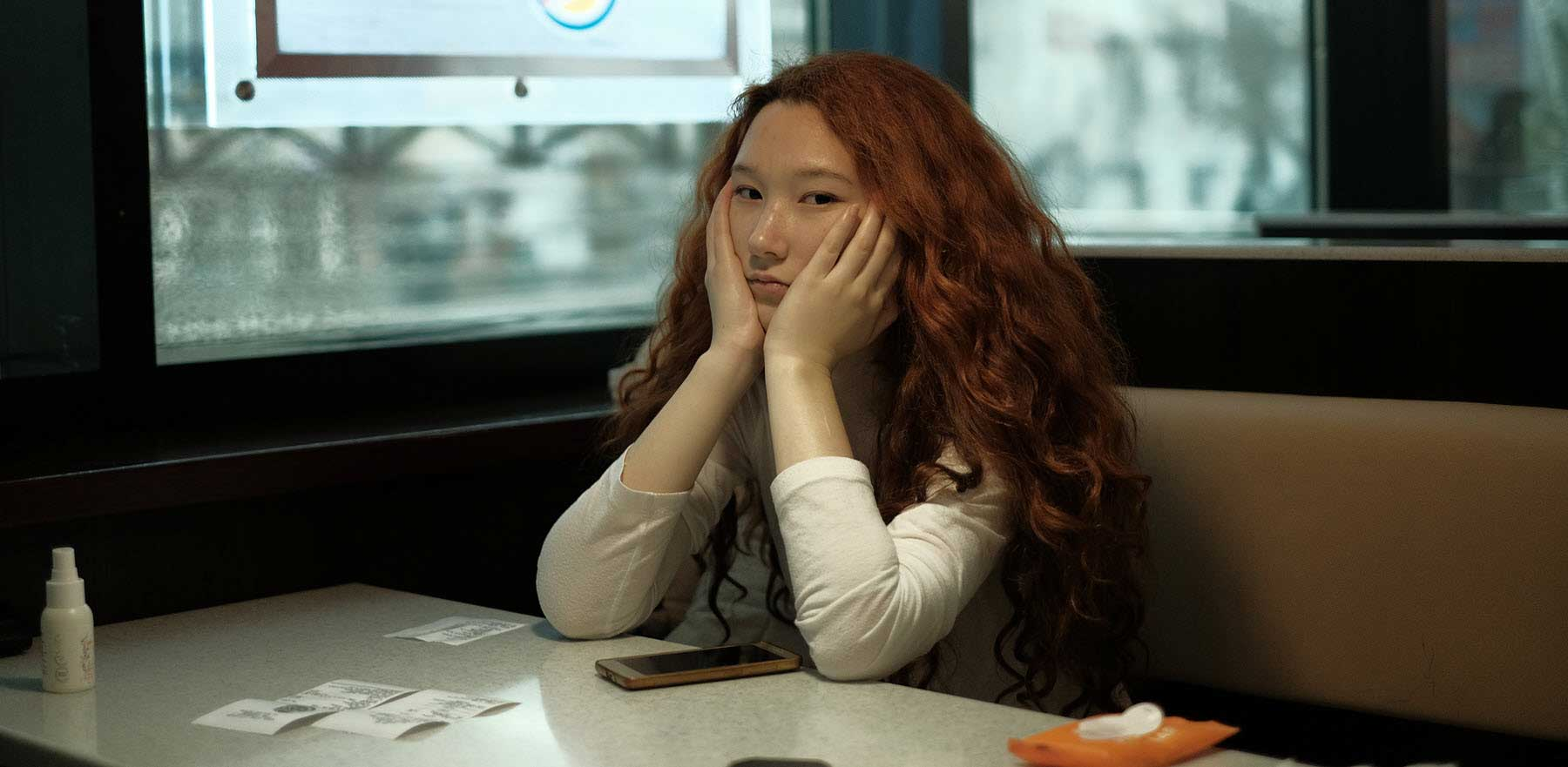 Girl-sitting-at-a-restaurant-struggling-with-forgiving-herself