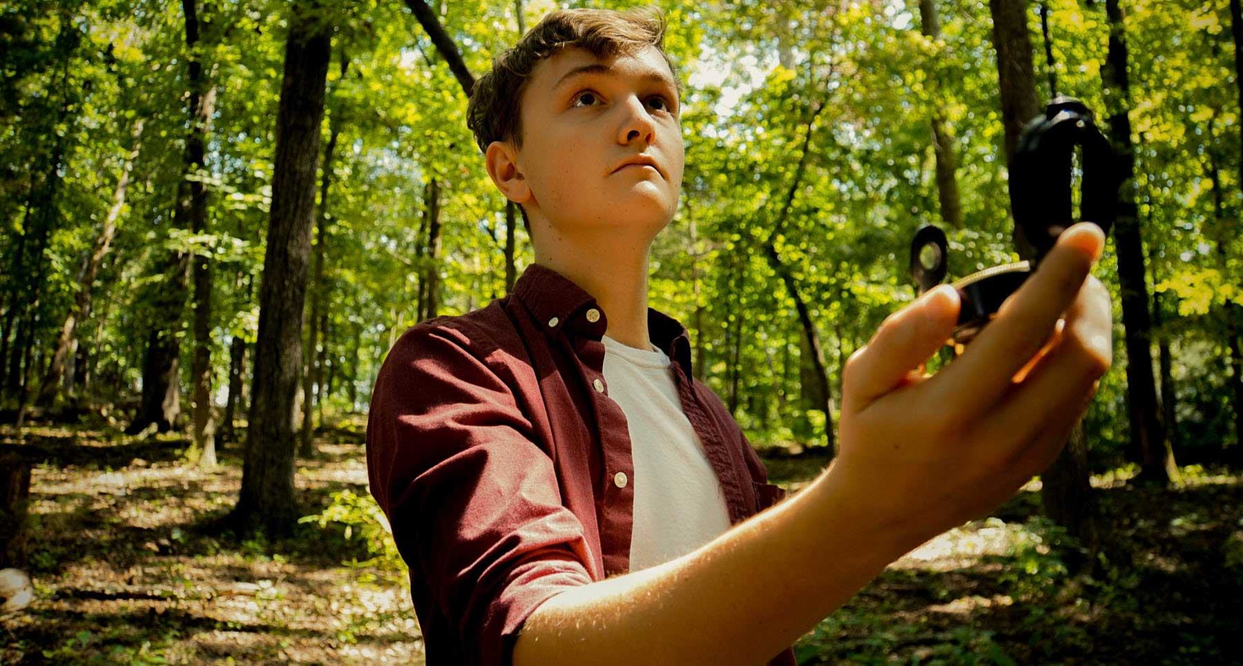 guy-standing-in-the-woods-with-a-compass-wanting-to-make-better-choices-in-life