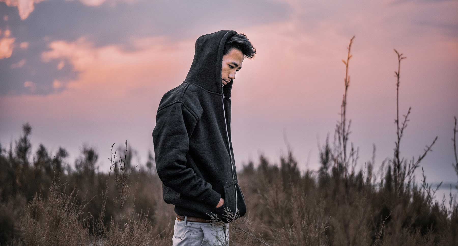 guy-in-a-hoodie-walking-outsied-and-sad-thehopeline-is-grief-wrong-unhealthy-grieving-after-loss