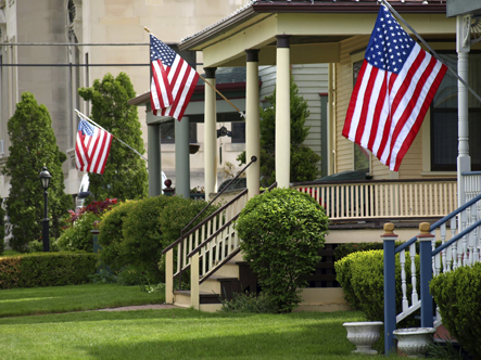 Image features a wide shot of a rural main street residential setting. The homes have American flags hanging in front of them.