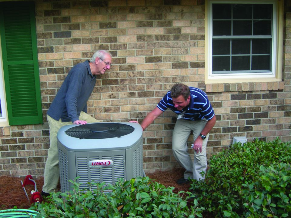 Image features an energy advisor inspecting a local homeowner's Air-Conditioning unit