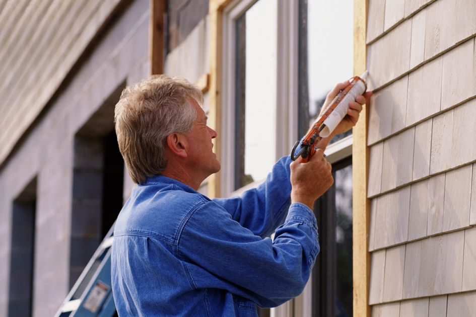 image features an image of a homeowner caulking his windows