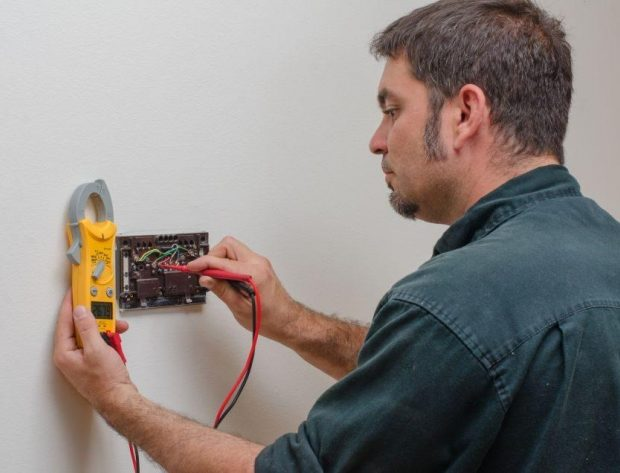 technician checking a thermostat