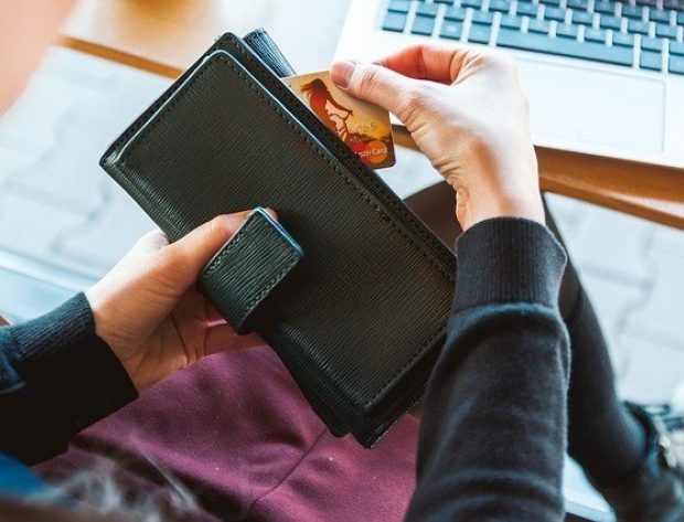 Pulling a credit card out of a wallet in front of a computer