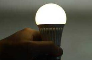 image of close-up shot of a hand, screwing in an LED lightbulb