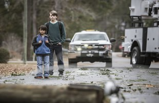 Image features two boys approaching downed power lines, following a summer storm