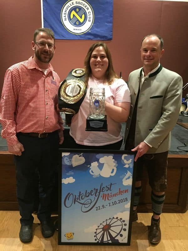 Emily showing off her championship belt and trophy with the owner and manager of Bavarian Bierhaus in Nashville.