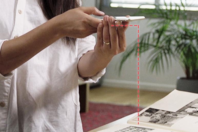 カメラを写真の真上に、テーブルと平行になるように手に持ってください。