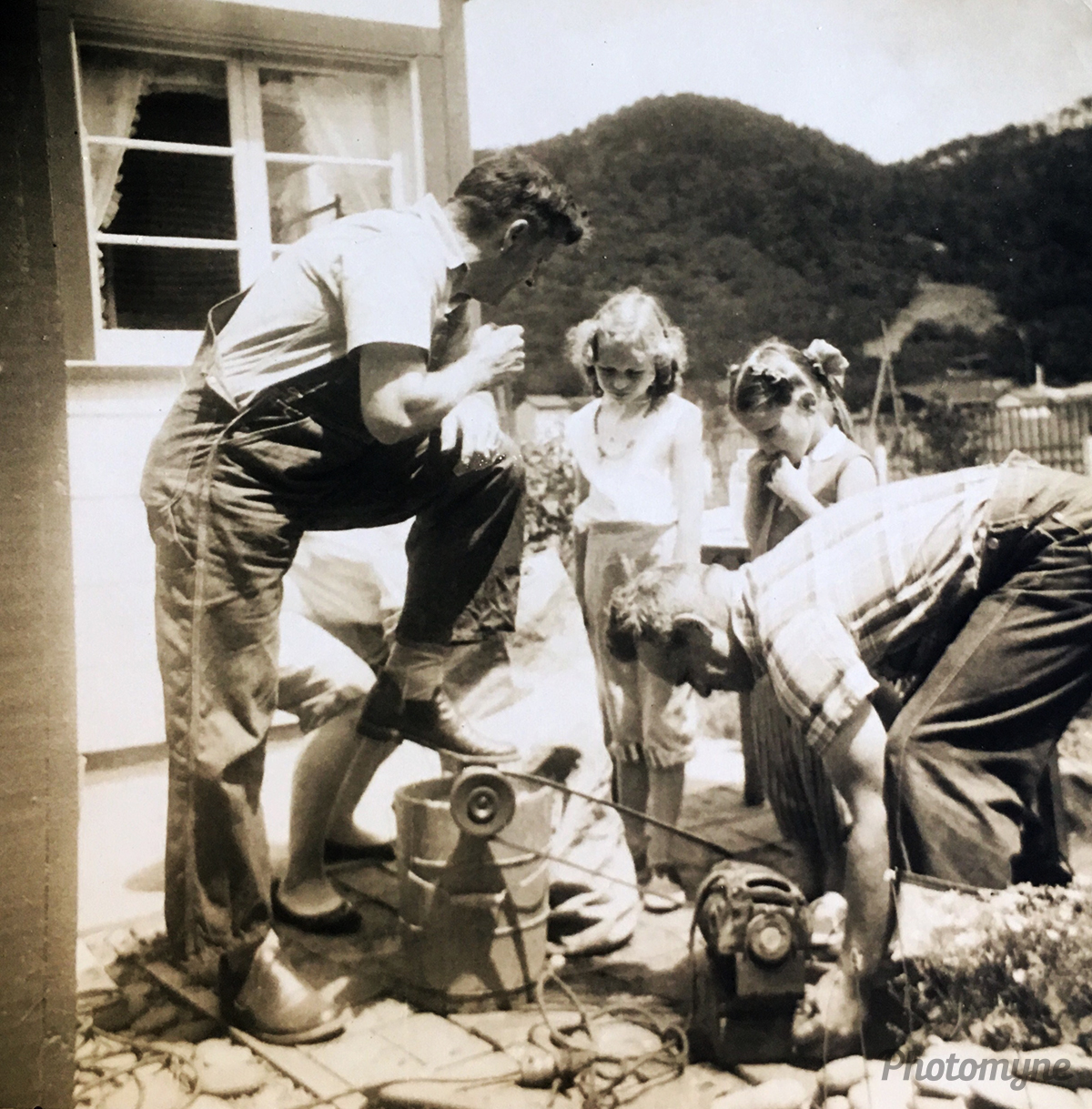 Men ingenuity- an electrician and mechanic solving the problem of how to get home made ice cream without hand churning. Pre electric ice cream makers. My father and his friend. Sister and I supervising. Oregon, USA 1958