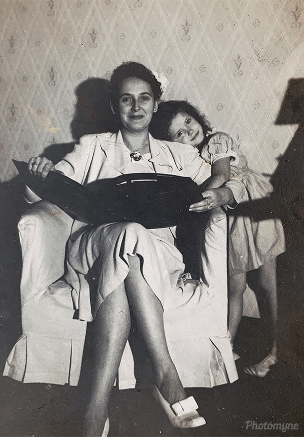 Mother and daughter looking at a photo album. USA 1944