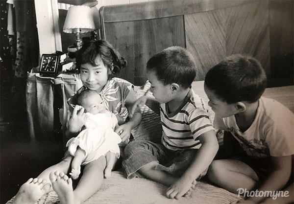 Aileen holding baby Michael with brothers Melvin and Milton looking on. Hawaii, USA 1956
