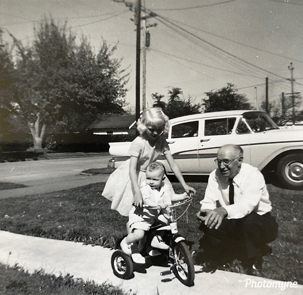 Big sister helping baby Michael ride a tricycle. Easter Sunday. USA 1962