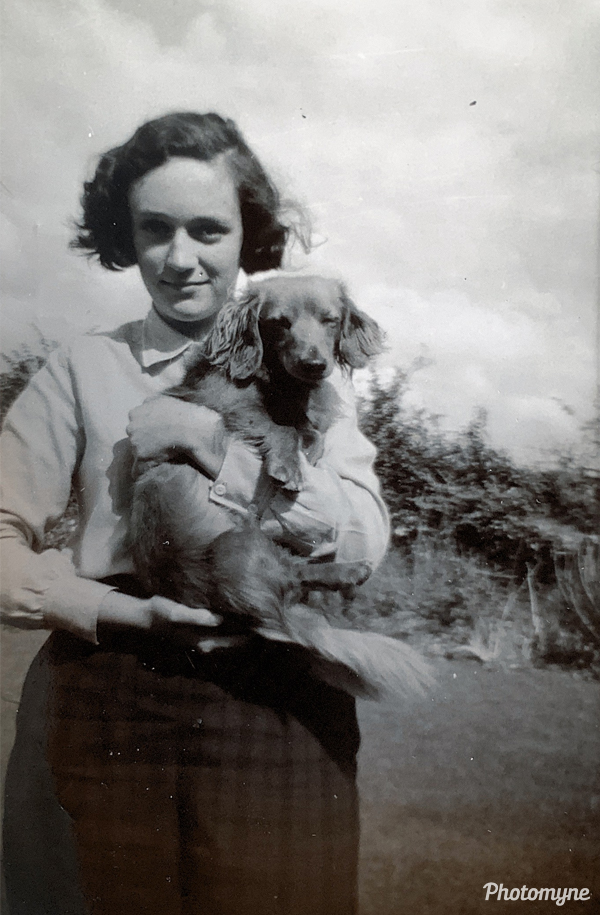 Anne at Singmore Farm with Chippy, the miniature, golden, long-haired dachshund. Great Britain 1960