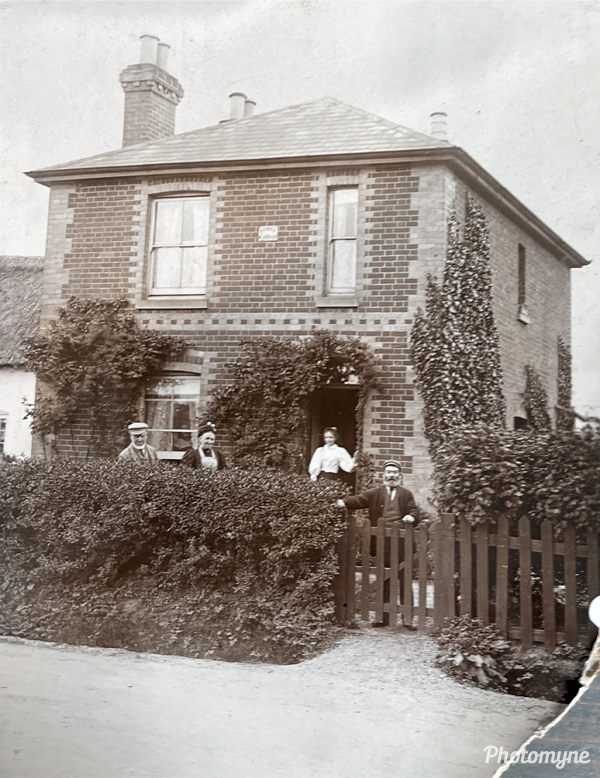 Fowey cottage in Peartree Green. Grandmother Edwards and Aunty May are at the front door, Grandfather Edwards is at the gate, and May Edwards is looking out the window. I don't know who the other man is. United Kingdom