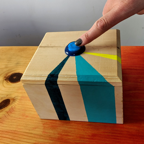 A wooden box with a blue button on the top sits on a table. The box has turquoise, teal, and neon yellow stripes and a finger is pointing at the button.