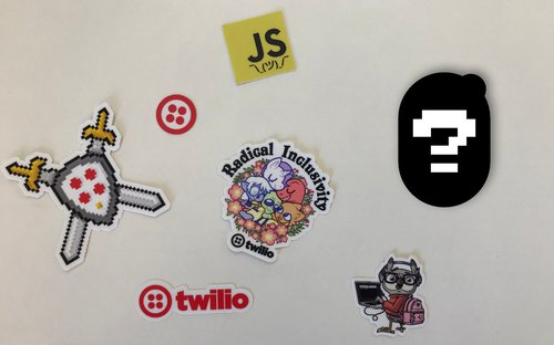 Photo of various Twilio stickers on a table with the outline of another sticker and a question mark on top of it