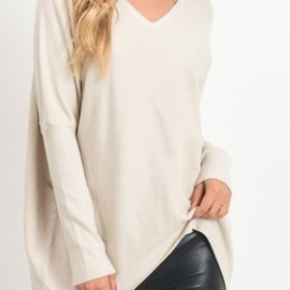 Solid mock-neck sweater top with keyhole cutout, long dolman sleeves, and hi-low hem.