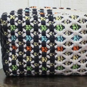 Multi colorful patterned origami make up bag with mini pom pom zipper closure detail.