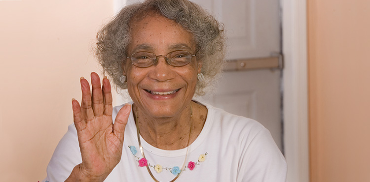Smiling elderly woman waving