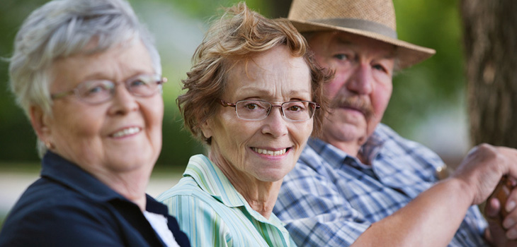 3 older people sitting on bench