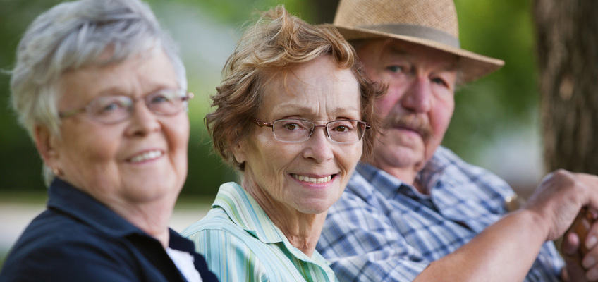 Three elderly people sitting on a park bench with trees in the background