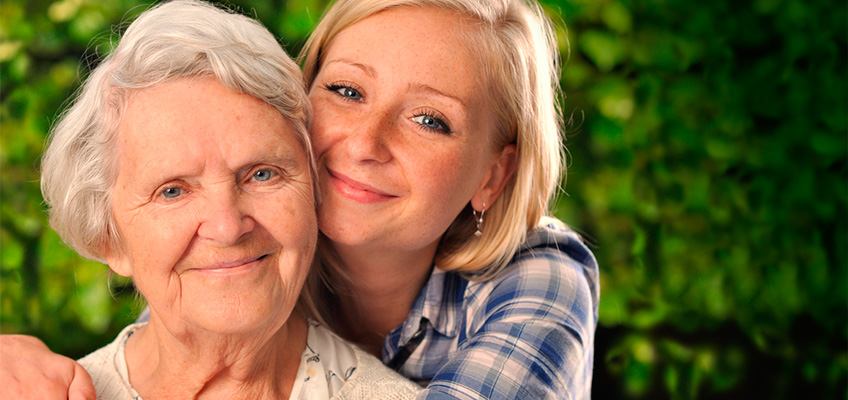 young woman with her arms around a smiling elderly woman