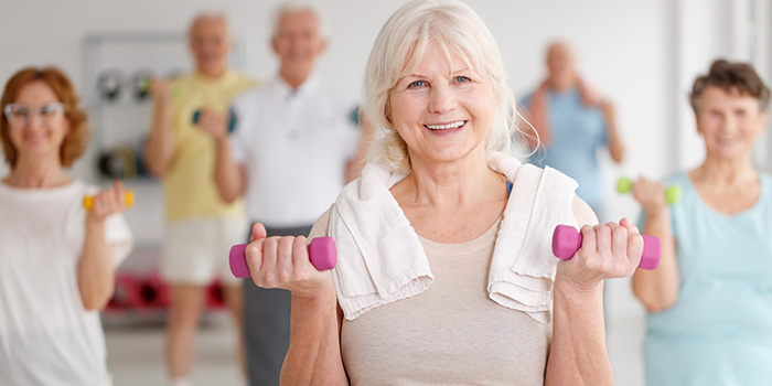 Group exercise class with male and female residents using hand weights and smiling