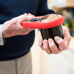 Skilled Nursing Facility man opening a can with a tool.
