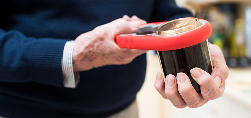 An older male trying to open up a can with a special tool.