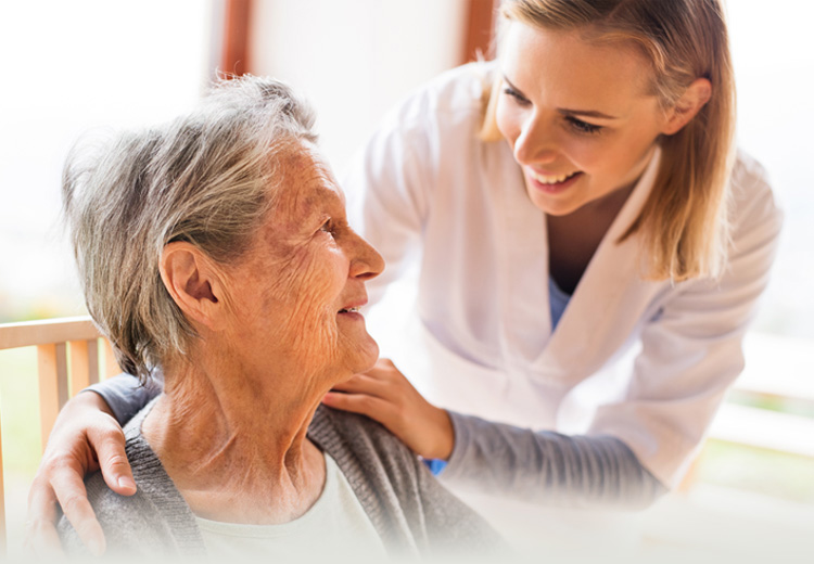 A senior and nurse smiling at each other.