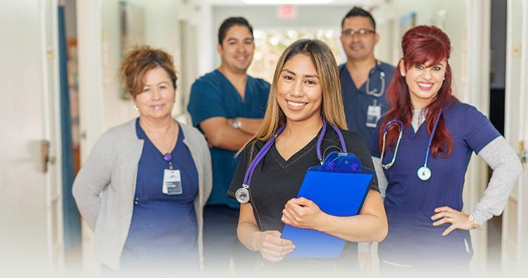 Nurses standing in a hallway smiling.