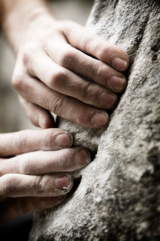 A climbers chalky hands on a boulder.