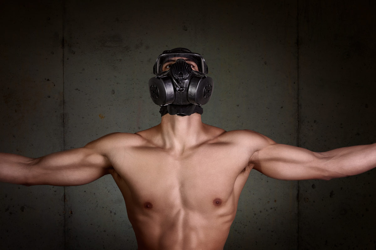 A shirtless man poses in a gas mask against a concrete wall