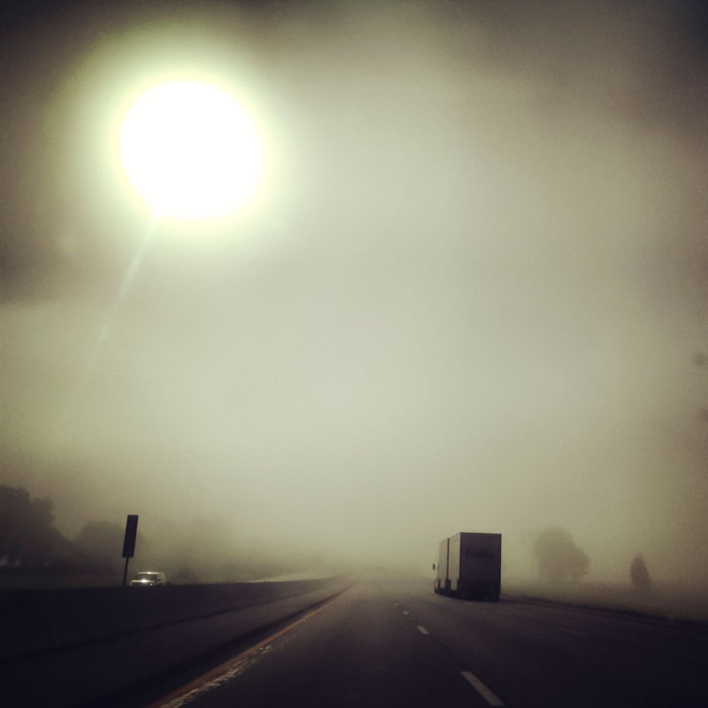 The sun shines through the fog on a highway.