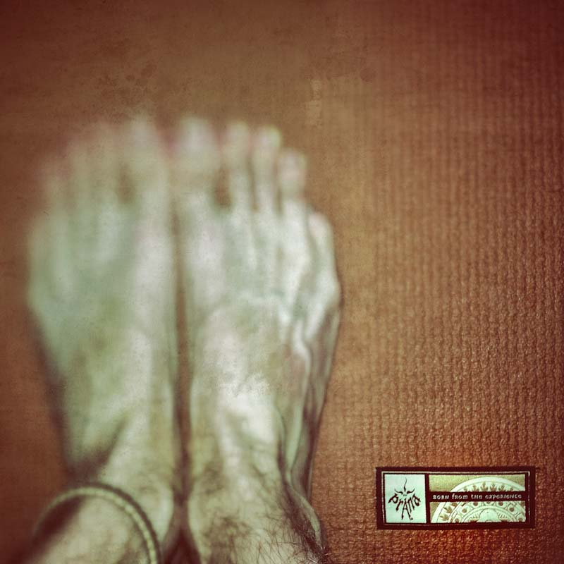 Feet on a Prana yoga mat.