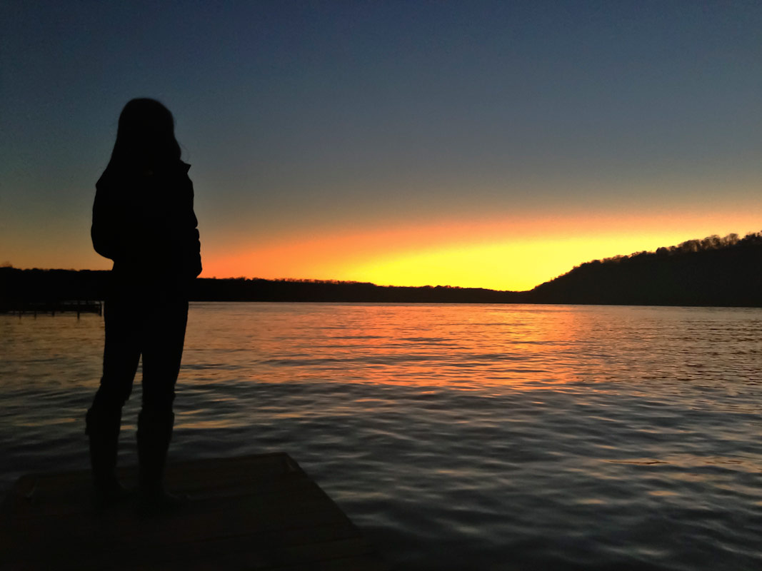 A silhouetted girl stands on a pier watching the sun set.