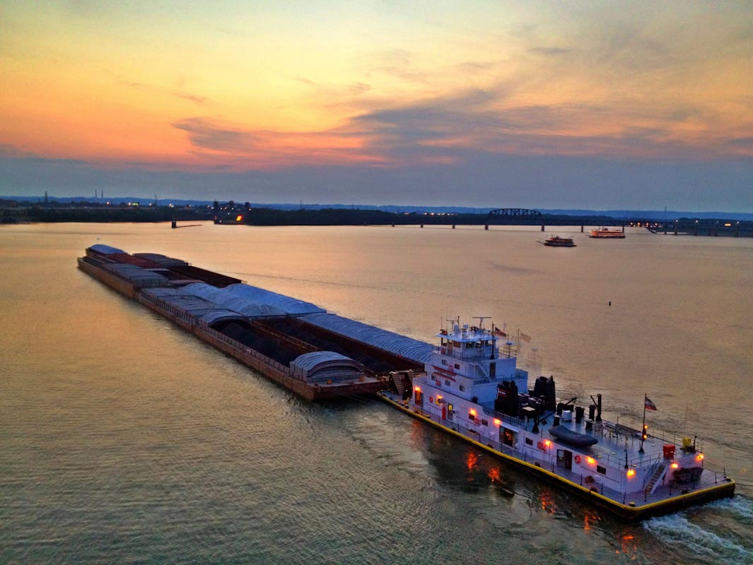 A barge passes by downtown Louisville , KY as it moves south along the Ohio River.