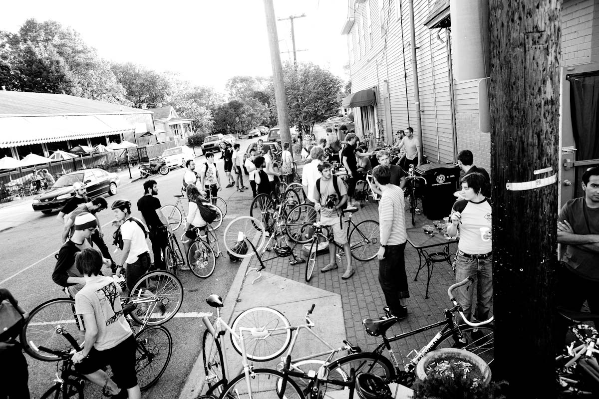 A crowd of cyclists prepare for an alley cat race.