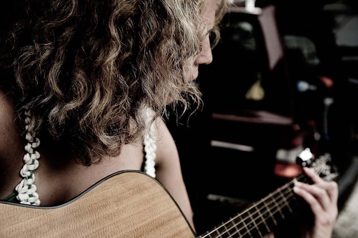 A woman plays a guitar.