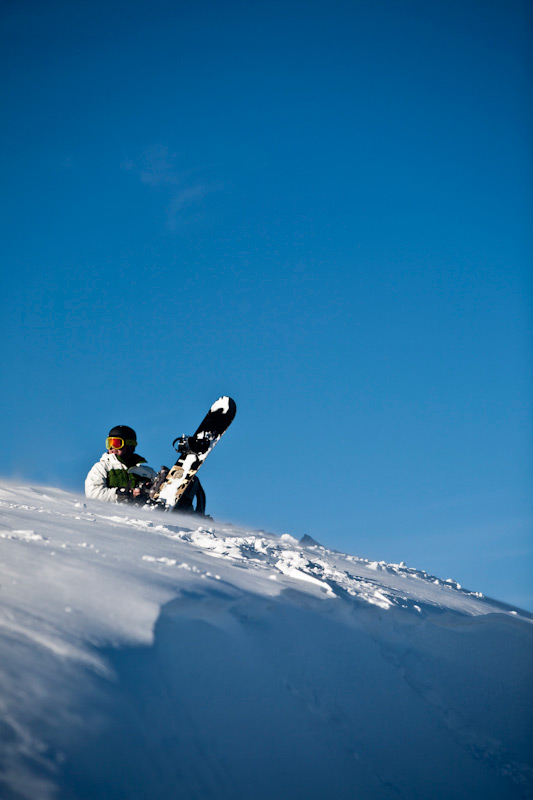 A man rests with his snowboard atop the mountain.